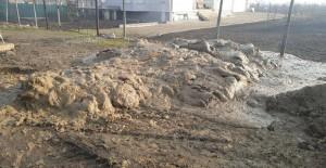 """Locuitorii din Cartierul Primăverii se străduies să creadă că """"meseriașii"""" angajați de Primărie basculează beton special, nu noroi."""